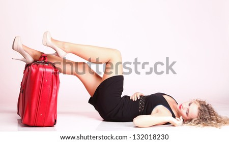 portrait of attractive caucasian woman blond wait red suitcase and rose - stock photo
