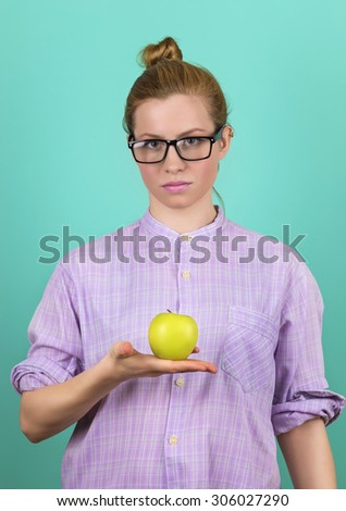 Portrait of attractive caucasian woman in glasses with an apple - studio shot  - stock photo