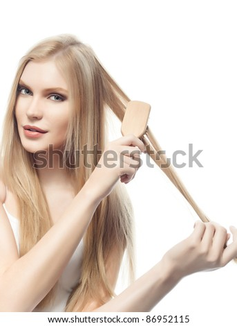 portrait of attractive  caucasian woman  with long blond hair isolated on white studio shot looking at camera with comb
