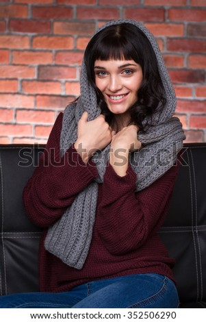 Portrait of attractive cheerful young woman in knitted gray scarf, sweater and jeans over brick wall background - stock photo