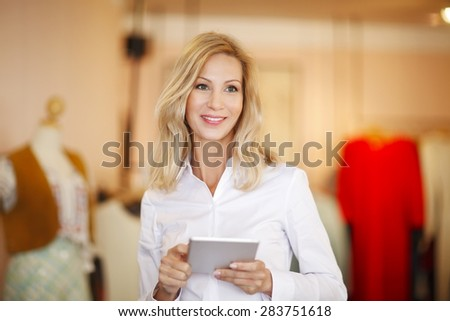 Portrait of attractive clothing store owner woman holding digital tablet in her hands and standing in store.  Small business. - stock photo