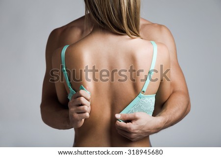 Portrait of attractive couple being intimate sitting down, while the man is undoing the woman's bra. - stock photo
