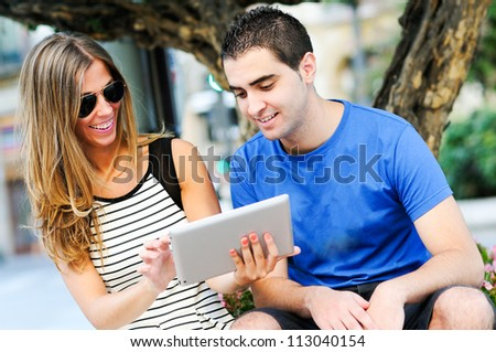 Portrait of attractive couple with tablet computer in urban background - stock photo