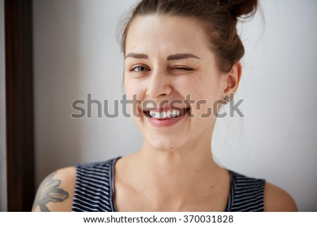 Portrait of attractive cute woman winking over gray background. Looking at the camera. Positive human emotion facial expression body language. Funny girl - stock photo
