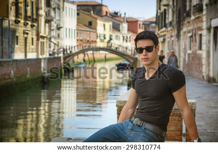 Portrait of Attractive Dark Haired Young Man Leaning Against Railing on Foot Bridge Over Narrow Canal in Venice, Italy - stock photo