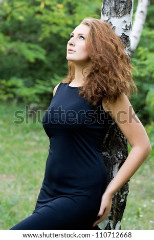 Portrait of attractive dark-haired young woman near birch tree at summer green park.