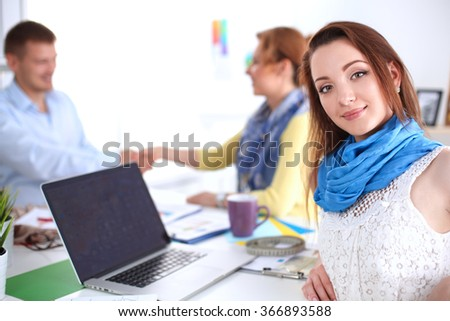 Portrait of attractive designers sitting on desk  in office