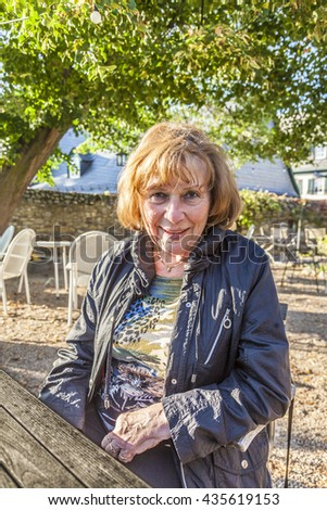 portrait of attractive elderly Lady in the park with red hair