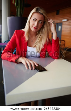 Portrait of attractive elegant woman sitting at cafe table pensive looking in to the distance, blonde businesswoman sitting in cafe with smart phone while dreaming, filtered image - stock photo