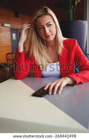 Portrait of attractive elegant woman sitting at cafe table pensive looking in to the distance, blonde businesswoman sitting in cafe with smart phone while dreaming - stock photo