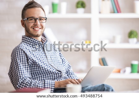 Portrait of attractive european guy in casual shirt and glasses using laptop computer at workplace