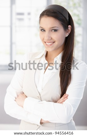 Portrait of attractive female college student smiling, standing arms crossed.? - stock photo