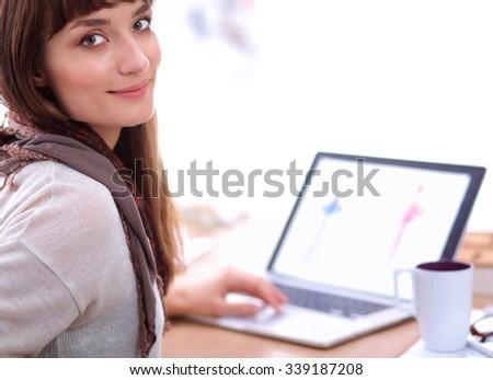 Portrait of attractive female fashion designer sitting at office desk - stock photo