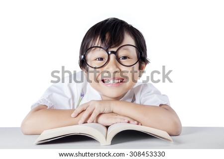 Portrait of attractive female kindergarten school student showing a toothy smile while wearing glasses, isolated on white - stock photo
