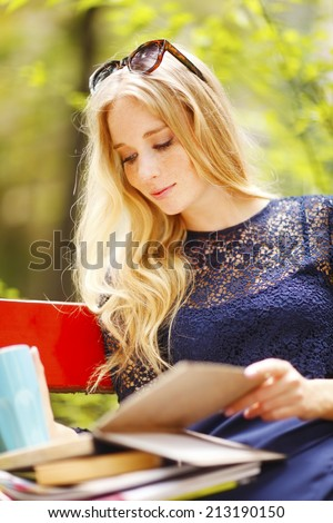 Portrait of attractive female student reading book, while sitting at campus area. Student life. - stock photo