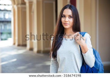 Portrait of attractive female student standing outdoors and lookign at camera - stock photo