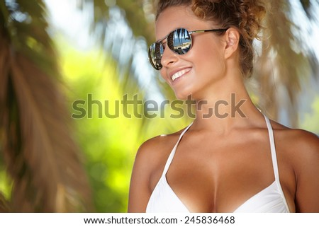 Portrait of attractive female wearing stylish sunglasses hug palm  - stock photo