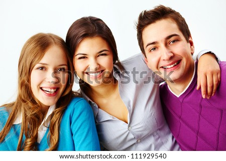 Portrait of attractive friends looking at camera and smiling - stock photo