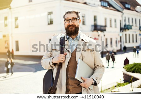 Portrait of attractive funny hipster man with beard, casual clothes walk in Europe.Trendy young man, urban street style.street fashion. Casual young businessman.male model in his 30s. Working - stock photo