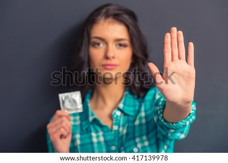 Portrait of attractive girl holding a condom, showing stop sign and looking at camera, against dark background. Hands in focus - stock photo