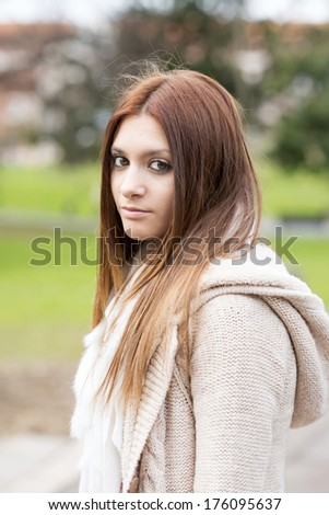 Portrait of attractive girl looking at camera, outdoor.
