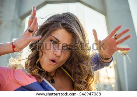 Portrait of attractive girl sitting on the street, raised hands,positive emotions, shining smile, enjoying life,attractive figure,cheerful.Rebel youth student concept