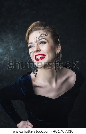 Portrait of attractive girl with art makeup posing on a dark background in the studio. Different emotions and poses. Quality Face Retouch. The huge size of the image.