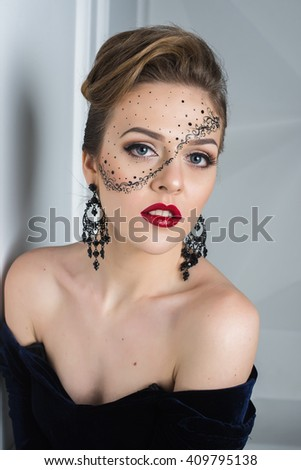 Portrait of attractive girl with art makeup posing on a white wall background in the studio. Different emotions and poses. Quality Face Retouch. The huge size of the image.
