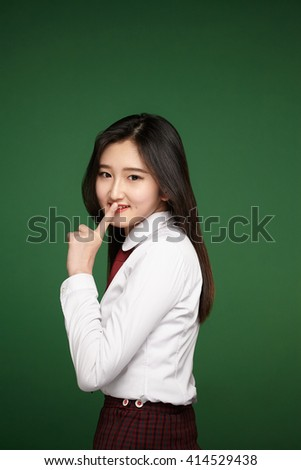 Portrait of attractive girl with finger on lips, concept of student show quiet, silence, secret gesture - stock photo