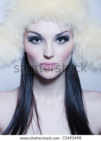Portrait of attractive girl with furry hat, studio isolated shot
