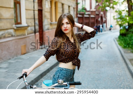Portrait of attractive girl with perfect slim body holding bicycle handlebar wearing denim shorts and shirt. On the street background.  - stock photo