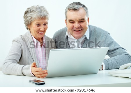Portrait of attractive grandmother and grandfather studying to use laptop - stock photo