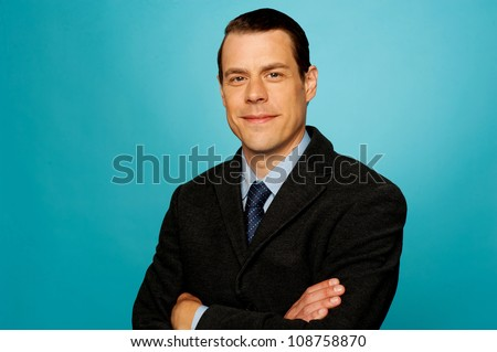 Portrait of attractive handsome businessman posing with arms crossed isolated over blue background - stock photo