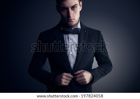 Portrait of attractive handsome stylish fashion young man in elegant casual classical suit with bow tie vogue style - stock photo