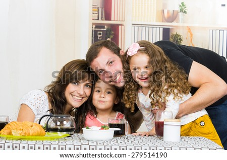 Portrait of attractive happy family with two little girls smiling