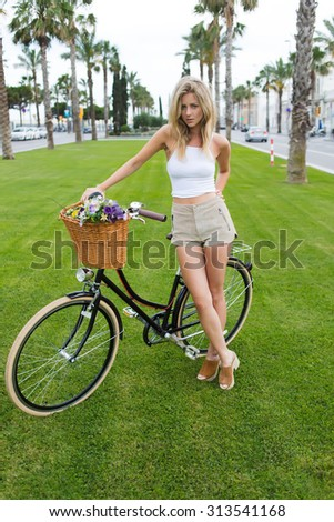 Portrait of attractive hipster woman dressed in stylish summer clothing posing with her classic bicycle, gorgeous female resting after riding in park on vintage bike with a basket of beautiful flowers - stock photo