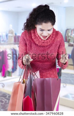 Portrait of attractive indian woman opens shopping bags in the shopping center - stock photo