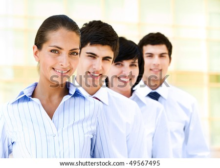 Portrait of attractive leader of friendly business group standing in line behind