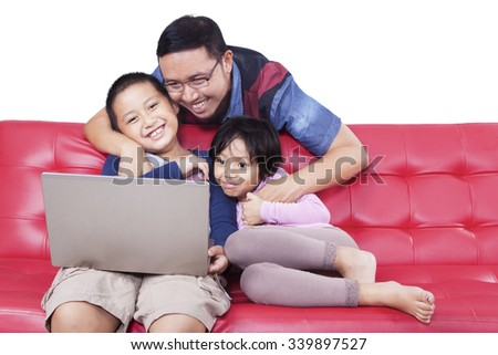 Portrait of attractive little children and their father enjoy movie with a laptop on the sofa, isolated on white