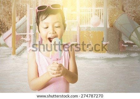 Portrait of attractive little girl holding a fresh ice cream on the pool, shot with an instagram effect - stock photo