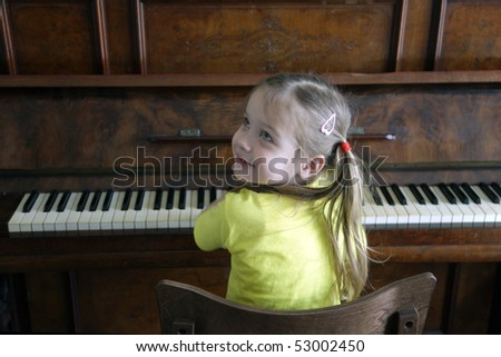 Portrait of attractive little girl, playing on piano