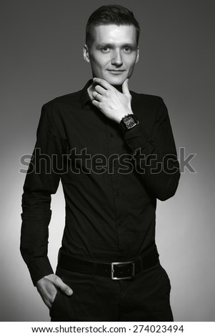 portrait of attractive macho man over grey background wearing a  wrist watch