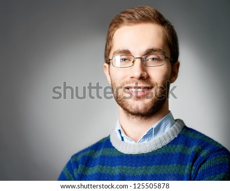 Portrait of attractive male in casual clothes and eyeglasses looking at camera with smile