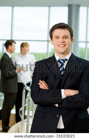 Portrait of attractive male in suit looking at camera with communicating associates on background