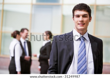 Portrait of attractive male in suit looking at camera with communicating associates on background - stock photo