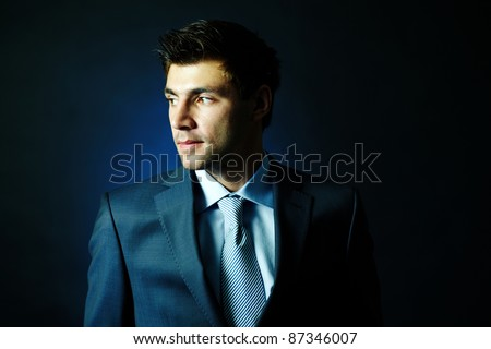 Portrait of attractive male looking aside in darkness - stock photo