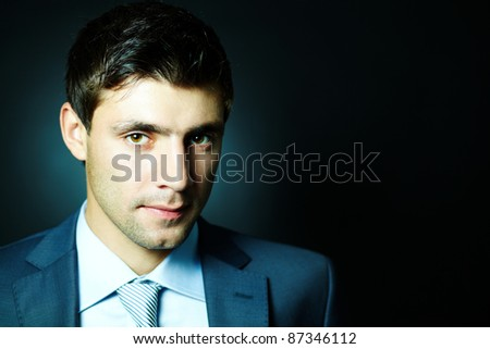 Portrait of attractive male looking at camera in darkness