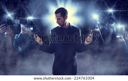 Portrait of attractive male vip celebrity posing in front of photographers paparazzi - stock photo