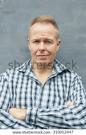 Portrait of attractive man at a blue wall