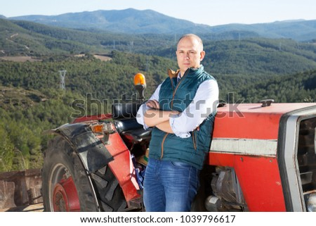 Portrait of attractive man near farm tractor in vineyard